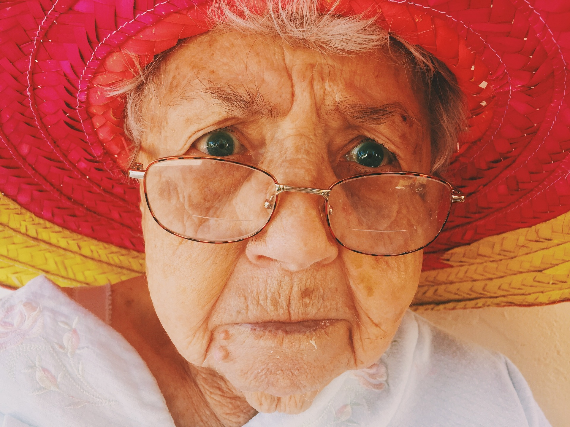 facial closeup of older woman with big hat, glasses down her nose, and serious expression
