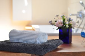 counter with folded towel and washcloth, and a flower arrangement behind