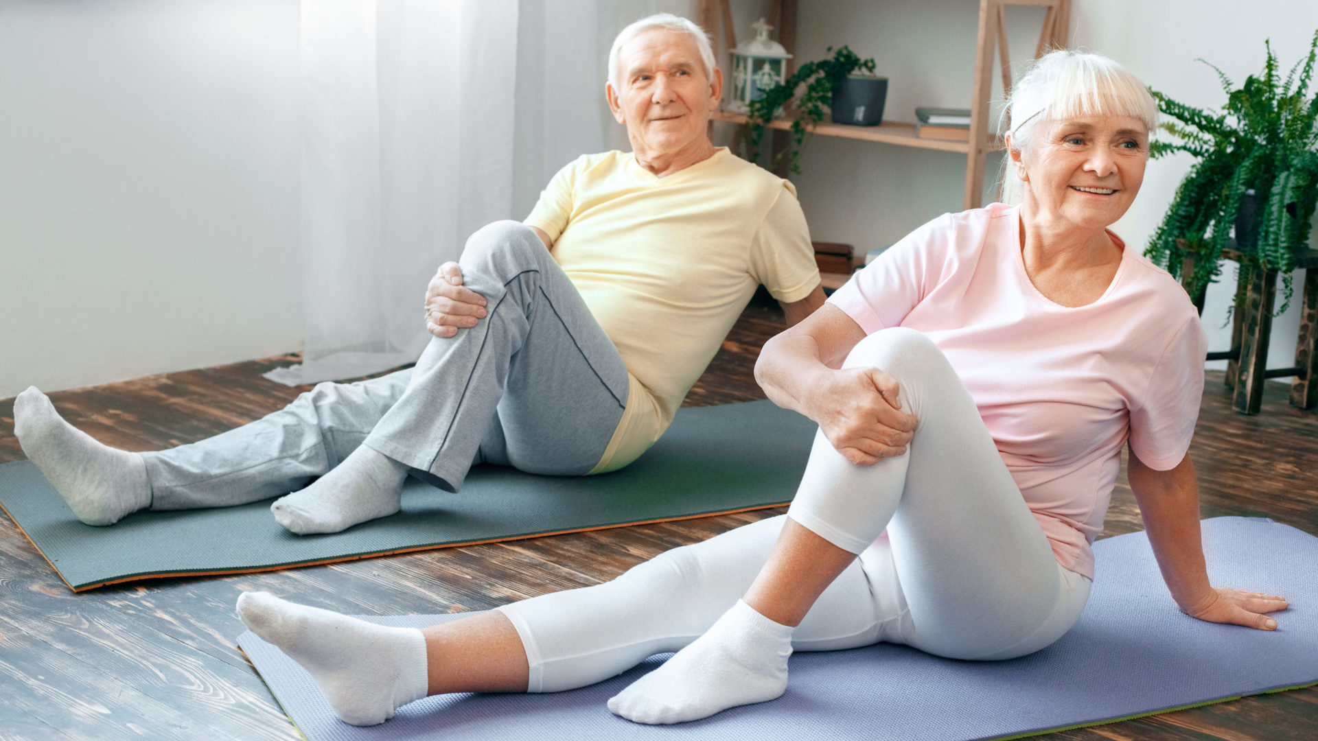 Senior man and woman doing yoga and stretching for exercise