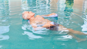 elderly man floating in the pool for exercise