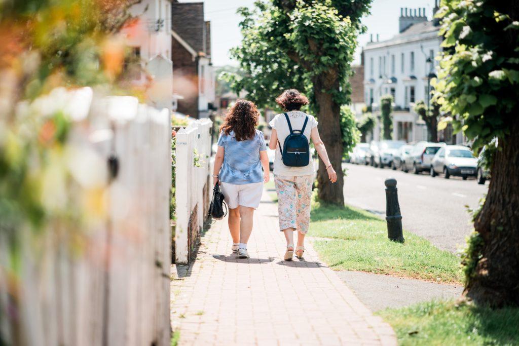 Two women walking down a sunny street