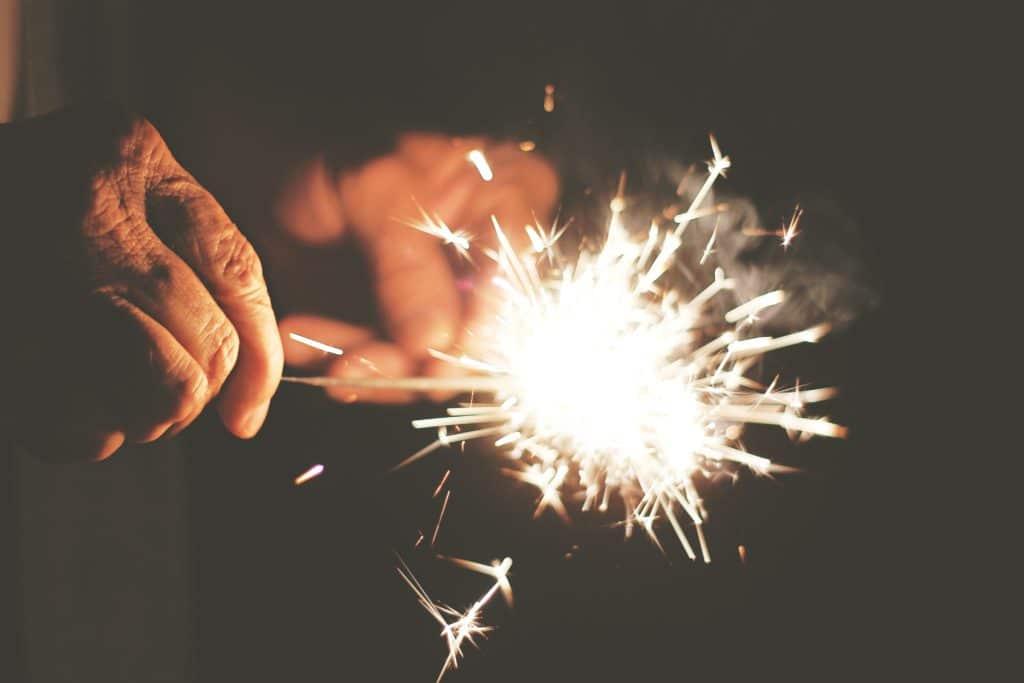 Older hands holding sparkler.