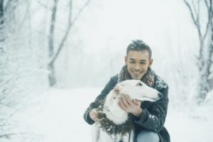 Man cuddling dog during a snowy walk.