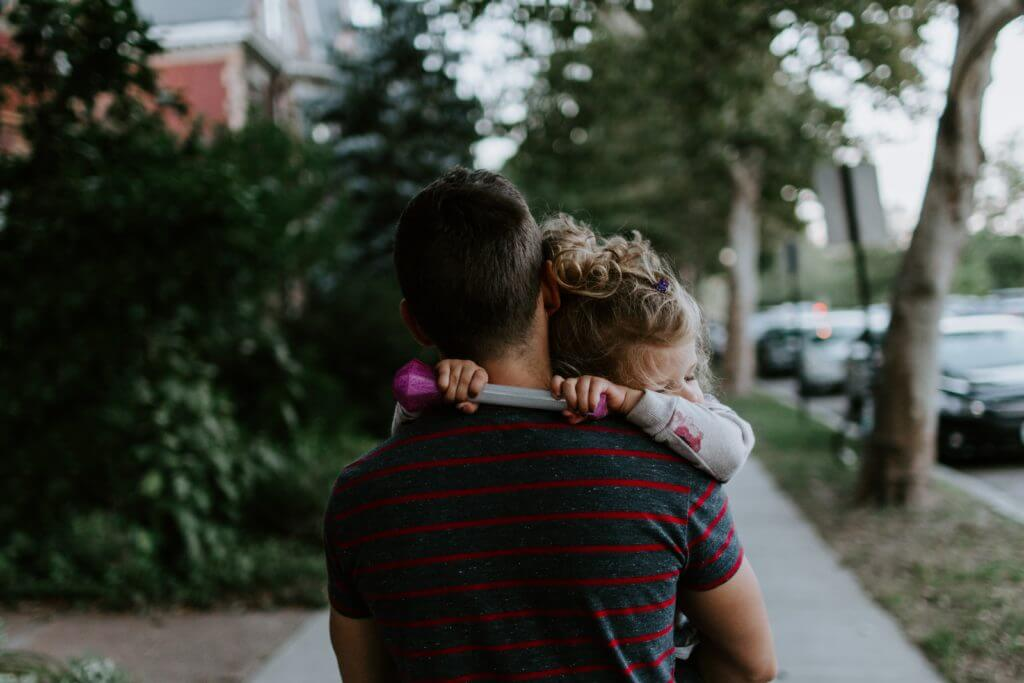 Man holding daughter in his arms, standing back-on.