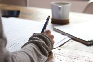 Hand writing on paper, wearing warm sweater.