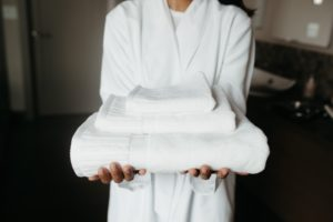 Person holding folded white towels.