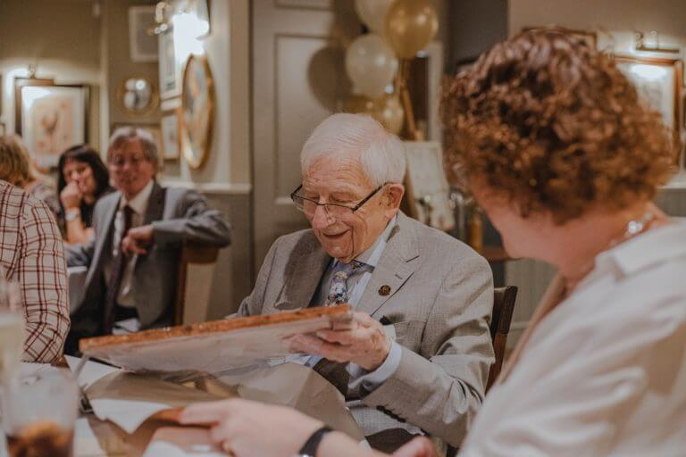 A 94-year-old enjoying a birthday party in his home.