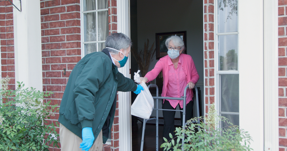 A man passing a bag to an elderly lady on her front porch.