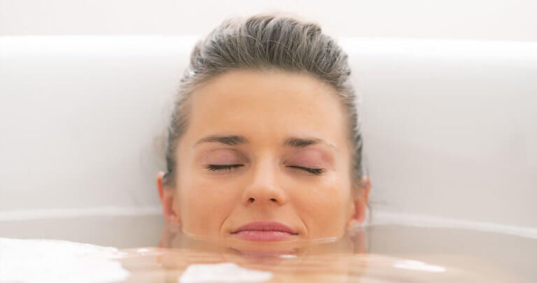 Person soaking neck and shoulders in a bathtub, relaxing